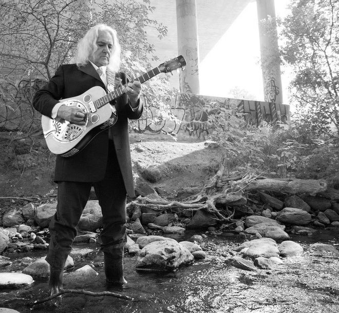 image of dennis o'toole playing a steel guitar standing in jackson creek