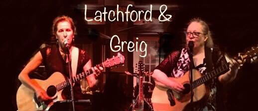 image of latchford and greig playing guitars together on stage at a cafe