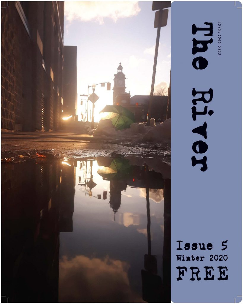 image of the cover of the river magazine issue five showing a low angle shot of charlotte street in peterborough pointing toward the market hall tower with the sun going down and glinting off of all the glass in the surrounding buildings